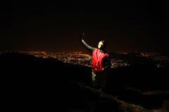 Hombre joven que toma el selfie encima de la colina observando la opinión de la ciudad de la noche Imagen de archivo