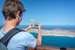 Hombre joven que toma imágenes con su smartphone, en Lanzarote España Fotos de archivo libres de regalías