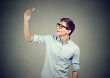 Hombre joven que toma imágenes de sí mismo con el teléfono elegante Fotos de archivo libres de regalías