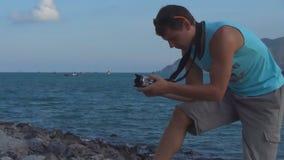 Hombre joven que toma imágenes en la cámara en la costa rocosa metrajes