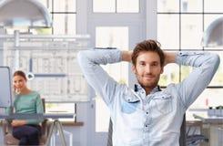 Hombre joven que toma la rotura del trabajo en la oficina de arquitecto