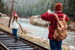 Hombre joven que toma las fotos de la novia en pista ferroviaria Foto de archivo libre de regalías