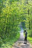 Hombre joven que toma las fotos en un bosque Fotos de archivo