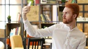 Hombre joven que toma Selfies en oficina con Smartphone almacen de video