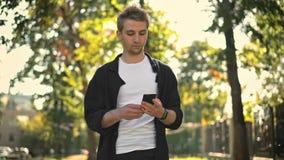 Hombre joven que toma smartphone del bolsillo y de mandar un SMS almacen de metraje de vídeo