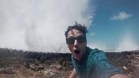 Hombre joven que toma un selfie, asombrosamente sobre soplo del agua del océano almacen de video