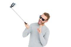 Hombre joven que toma un selfie con el palillo del selfie Foto de archivo