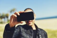 Hombre joven que toma un selfie con su smartphone Foto de archivo