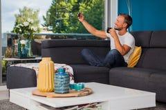 Hombre joven que toma un selfie mientras que bebe el café en el sofá fotografía de archivo