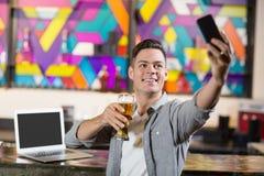 Hombre joven que toma un selfie mientras que comiendo un vidrio de cerveza Fotografía de archivo libre de regalías