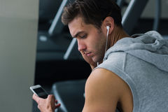 Hombre joven que toma una rotura después de su entrenamiento y que escucha la música en su teléfono Fotografía de archivo libre de regalías