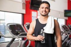 Hombre joven que toma una rotura en el gimnasio Imagen de archivo