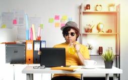 Hombre joven que trabaja con el ordenador portátil y el zumo de naranja de consumición en Summe imágenes de archivo libres de regalías