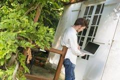 Hombre joven que trabaja con su ordenador portátil debajo de la pérgola Imagen de archivo libre de regalías