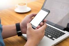 Hombre joven que trabaja de hogar usando el teléfono elegante Imágenes de archivo libres de regalías
