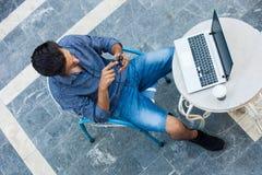 Hombre joven que trabaja de terraza con el ordenador portátil y el smartphone fotografía de archivo