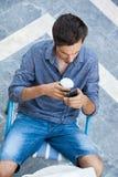 Hombre joven que trabaja de terraza con smartphone imagen de archivo libre de regalías