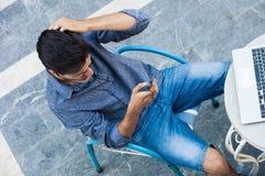 Hombre joven que trabaja de terraza con smartphone y el ordenador portátil imagen de archivo