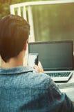 Hombre joven que trabaja de terraza con smartphone y el ordenador portátil foto de archivo