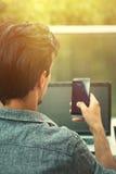 Hombre joven que trabaja de terraza con smartphone y el ordenador portátil imagen de archivo libre de regalías