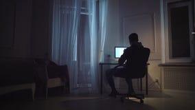 Hombre joven que trabaja en el guión en el ordenador en el sitio de noche, gato en travesaño de la ventana metrajes