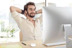 Hombre joven que trabaja en el ordenador Imagenes de archivo