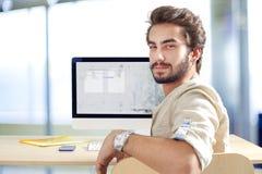 Hombre joven que trabaja en el ordenador Imágenes de archivo libres de regalías
