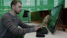 Hombre joven que trabaja en el ordenador en la oficina almacen de video