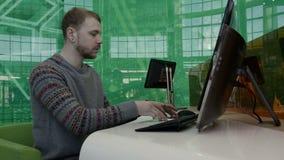 Hombre joven que trabaja en el ordenador en la oficina almacen de metraje de vídeo