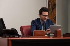 Hombre joven que trabaja en el ordenador en oficina Foto de archivo libre de regalías