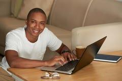 Hombre joven que trabaja en el ordenador portátil foto de archivo libre de regalías