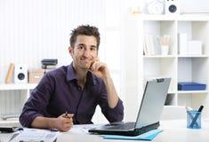 Hombre joven que trabaja en el ordenador portátil Imagenes de archivo