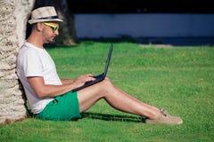 Hombre joven que trabaja en el ordenador portátil al aire libre Fotografía de archivo