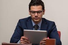 Hombre joven que trabaja en panel táctil en oficina Fotografía de archivo libre de regalías