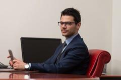 Hombre joven que trabaja en panel táctil en oficina Imágenes de archivo libres de regalías