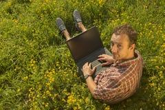 Hombre joven que trabaja en su ordenador portátil al aire libre Imagen de archivo