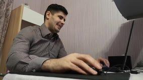Hombre joven que trabaja en su ordenador portátil y que se ríe de lo que él vio en la pantalla de ordenador almacen de metraje de vídeo