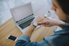 Hombre joven que trabaja en un macbook o un ordenador portátil en café Imagen de archivo libre de regalías