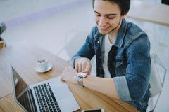 Hombre joven que trabaja en un macbook o un ordenador portátil en café fotos de archivo