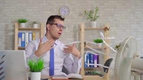 Hombre joven que trabaja en un ordenador portátil en la oficina que se sienta delante de la fan MES lento metrajes