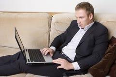 Hombre joven que trabaja en una computadora portátil Imagenes de archivo