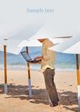 Hombre joven que trabaja remotamente debajo del paraguas fotos de archivo libres de regalías