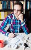 Hombre joven que trabaja y que piensa en el lugar de trabajo Imágenes de archivo libres de regalías