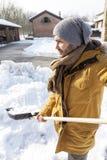 Hombre joven que traspala nieve cerca de una granja Imágenes de archivo libres de regalías