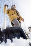 Hombre joven que traspala nieve cerca de una pequeña madera Imagenes de archivo