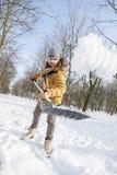 Hombre joven que traspala nieve cerca de una pequeña madera Fotografía de archivo libre de regalías