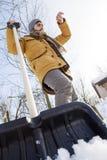 Hombre joven que traspala nieve cerca de una pequeña madera Fotos de archivo libres de regalías