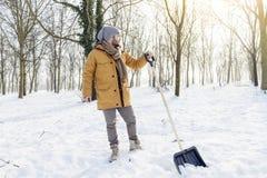 Hombre joven que traspala nieve cerca de una pequeña madera Foto de archivo