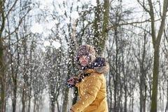 Hombre joven que traspala nieve cerca de una pequeña madera Imagen de archivo