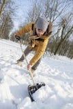 Hombre joven que traspala nieve cerca de una pequeña madera Fotos de archivo